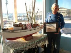 Grand Opening-Angelo Tringali, holding a picture of his father's boat C. 1920's standing next to the boat model he donated.jpg